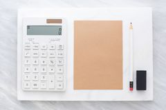 Top view of calculator, pencil, eraser and brown notepad on whi. Te marble block and stack on grey marble table.Flat lay Mock up template for adding or display royalty free stock images