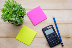 Top view calculator,post it note,pencil and some plant put on wo. Oden background Royalty Free Stock Image
