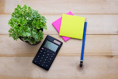 Top view calculator,post it note,pencil and some plant put on wo. Oden background Stock Photos