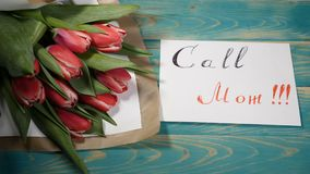 Top view of a Call Mom message note and tulips flowers bouquet on a wooden table. Love relationship concept. Mother day. 4 k stock video footage