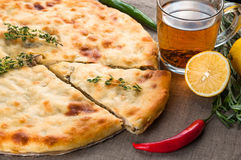 Top view of calzone pizza or chicken mushroom pie. With pepper, lemon, rosemary and tea Royalty Free Stock Photos