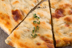 Top view of calzone pizza or ossetian chicken pie. Slice of calzone pizza or ossetian chicken pie and thyme macro close up Royalty Free Stock Photos