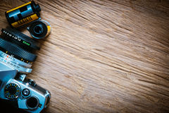 Top view of camera with film rolls on wooden floor. Stock Photos