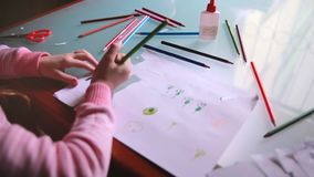 Top view camera sliding left on little Caucasian girl child drawing on paper with various color pencils at a table. stock video