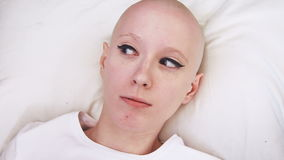 Top view of a cancer patient woman lying in the bed, wakes up and is scared and concerned