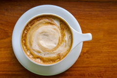 Top view of cappuccino coffee cup with milk foam on wood backgro Stock Image