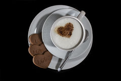 Love Coffee. Top view of Cappuccino Coffee with love heart chocolate sprinkles and three heart shaped biscuits with the word Love royalty free stock images