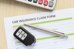 Top view of car insurance claim form with car key and pen on wooden desk Royalty Free Stock Photos