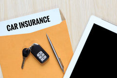 Top view of car insurance in envelope with car remote key, pen a Stock Photo
