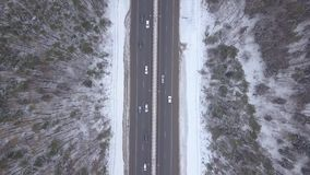 Top view car traffic on winter highway. Cars and trucks driving on winter road. Through snowy forest aerial landscape. Drone view car moving on blizzard road stock video footage