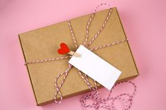 Cardboard box with cloth pin with red heart and empty white label. Top view cardboard box with cloth pin with red heart and empty white label with place for text royalty free stock image