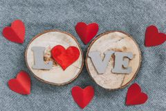 Top view cardboard letters LOVE and paper hearts. On a wooden and knitted background stock photos
