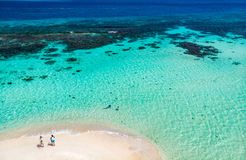 Top view of Caribbean island. Aerial drone view of tiny tropical Mopion island sandbar, turquoise Caribbean sea and a family with kids in St Vincent and royalty free stock image