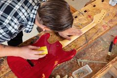 Top view of craftsman sanding a guitar neck in wood at workshop. Top view of carpenter using sanding paper on a guitar neck in a workshop for wood. Hard working stock photo