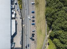 Aerial view of a cars by a warehouse. Top view of cars and vehicles on main road by a warehouse. Elevated drone photography Stock Photo