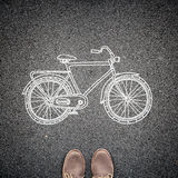 Top view of casual man's shoes and a sketched model of a bicycle on asphalt. A concept of environmental friendly way of travelling Royalty Free Stock Images