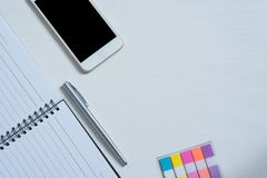 Top view of Cellphone ,  Open book, pen, mini colorful paper note. On bright wooden table stock photo