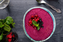 Top view Ceramic bowl with berry smoothie decorated with currant, raspberry and mint on the black wooden background - Well being,. Healthy eating, Detox or Diet Stock Photo