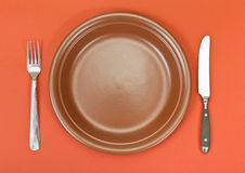 Top view of ceramic plate, fork, knife on red Royalty Free Stock Photos