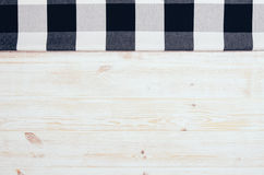 Top view of checkered cloth napkin on white wooden table. Top view of black checkered napkin or tablecloth on white wooden table with visible planks, texture and Stock Image