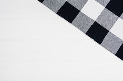 Top view of checkered cloth napkin on white wooden table. Top view of black checkered napkin or tablecloth on white wooden table with visible planks, texture and Royalty Free Stock Photos