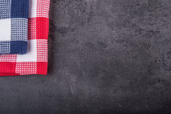 Top view of checkered kitchen tablecloth on granite -  concrete - stone background. Free space for your text or products Stock Photo