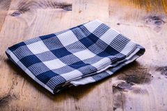 Top view of checkered kitchen towels on wooden table Stock Photos
