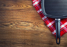 Top view of checkered napkin and teflon pan on wooden table. Royalty Free Stock Photo