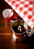 Top view of checkered napkin on wooden table with red coffee cup Stock Photography