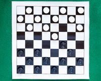 Top view of checkers on black and white sheet. Top view of checkers on black and white checkered sheet board on green baize table royalty free stock photography