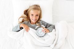 Top view of cheerful blonde girl lying in bed with alarm clock,. Looking at camera Royalty Free Stock Photos