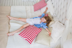 TOP VIEW: Cheerful little girl lies in a bed Royalty Free Stock Image