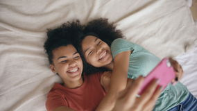 Top view of cheerful mixed race funny sisters making selfie portrait on bed in bedroom at home. Top view of cheerful mixed race funny girls making selfie stock video