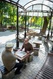 Joyful senior men playing checkers outdoor Stock Photo