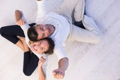 Couple sitting with back to each other on floor. Top view of Cheerful young couple sitting with back to each other on floor Stock Image