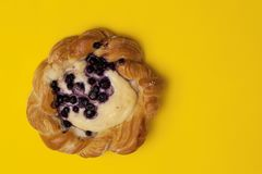Top view of cheese danish puff pastry with blackberries and vanilla custard on punchy yellow background stock image