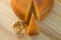 Top view of cheese wheel and slice with nuts over a wooden table Stock Photo