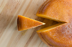Top view of cheese wheel and slice over a wooden table Stock Photo