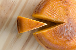 Top view of cheese wheel and slice over a wooden table Stock Photography