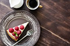 Top view cheesecake with raspberries, cup of coffee and cream on wood. Copy space for text Royalty Free Stock Images