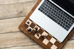 Top view of chess board, laptop and chess pieces on rustic stock photo