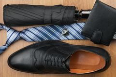 Top view, chic classic men`s shoes, tie, wallet, umbrella and cufflinks. On the wooden desk Royalty Free Stock Photos
