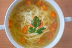 Top view for chicken broth with nudles, carrot and and parsley. Royalty Free Stock Photography