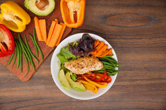 Top view of a chicken dish for dinner. Flat lay of a dish with chicken sitting on a bed of vegetables and some of its ingredients on the side with a lot of copy Royalty Free Stock Images