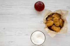 Top view, chicken nuggets in a paper box, ketchup and glass of cold beer on a white wooden background. Overhead, from above, flat. Lay. Copy space stock photography