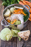 Top view of chicken soup -  broth on wooden table with vegetable. Carrot celery onion. Fresh vegetable on old oak wooden table Royalty Free Stock Image