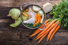 Top view of chicken soup -  broth on wooden table with vegetable. Carrot celery onion. Fresh vegetable on old oak wooden table Stock Photography