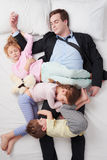 Top view of chidren sleeping all over father. Top view photo of tired businessman wearing suit, and his three children. Chidren sleeping all over father Stock Image