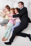 Top view of chidren sleeping with father. Top view photo of tired businessman wearing suit, and his three children. Father hugging his daughters and son. Chidren Stock Photography