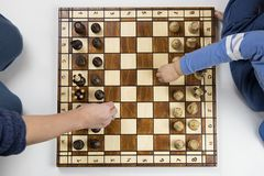 a top view of a child and an adult playing chess on white background stock photography